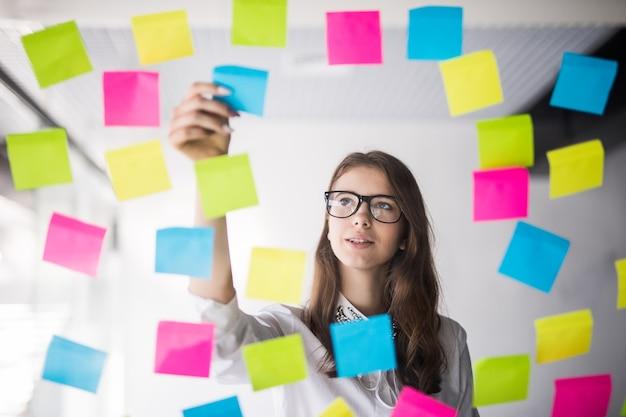 Giovane ragazza donna d'affari con gli occhiali guarda sulla parete trasparente con un sacco di adesivi di carta su di esso Foto Gratuite