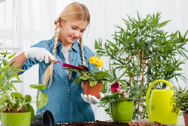 Young girl caring flowers in greenhouse Free Photo