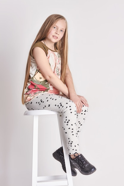 Young girl child with long hair sitting on a chair. smile joy emotions on her face Premium Photo