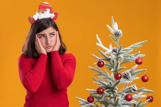 Giovane ragazza in maglione di natale indossando la fascia divertente che osserva da parte confusa e molto ansiosa accanto a un albero di natale su sfondo arancione Foto Gratuite