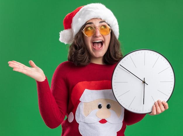 Giovane ragazza in maglione di natale che indossa il cappello e occhiali della santa che osserva in su l'orologio di parete della tenuta felice ed emozionante che sta sopra la parete verde Foto Gratuite