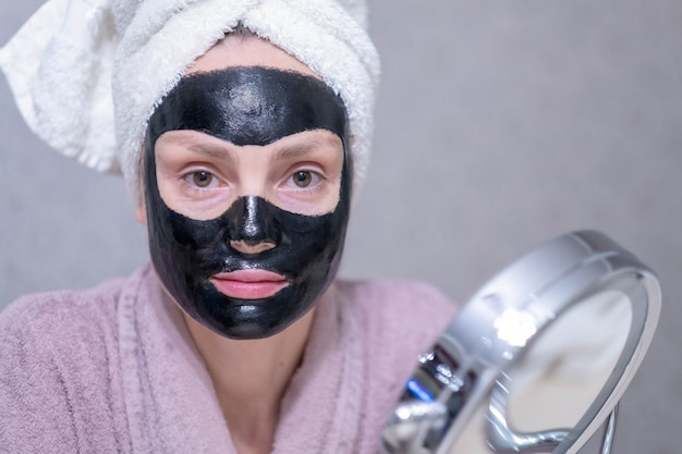 Young girl in a cleansing black coal mask on her face. Premium Photo