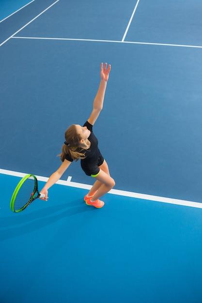 La ragazza in un campo da tennis chiuso con la palla Foto Gratuite