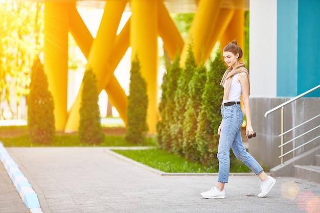 Молодая девушка спускается по лестнице в летний день. полная высота. Premium Фотографии