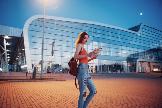 若い女の子は、空港または駅のターミナルの近くで、市内地図を読んだり、ホテルを探したりして、夜にかかります。バックパックを持つかわいい観光客が旅行の概念を決定します 無料写真