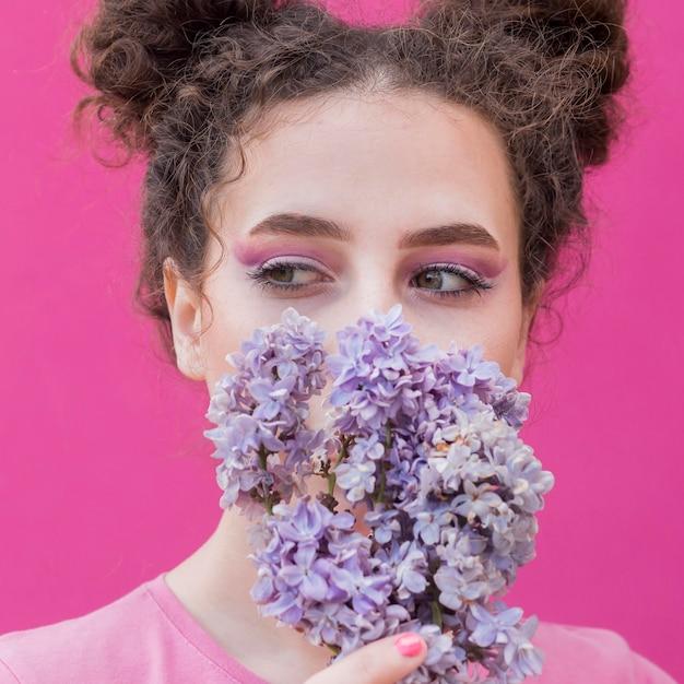 Ragazza che copre il viso di fiori lilla Foto Gratuite