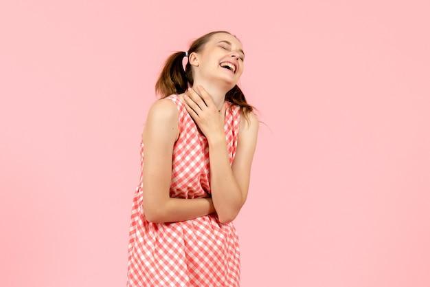 Giovane ragazza in abito rosa carino con espressione ridente sul rosa Foto Gratuite