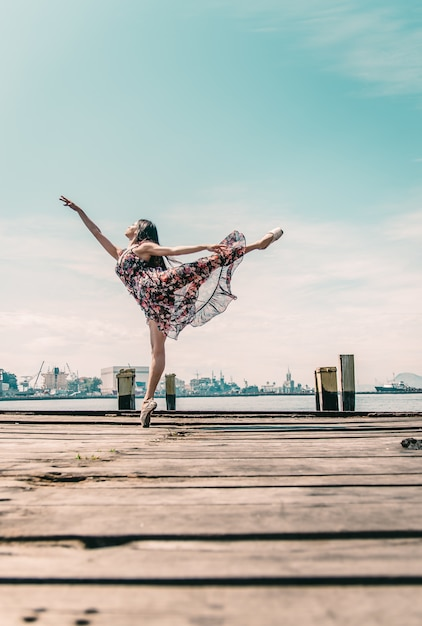 Young girl dancing on boardwalk in the waterfront Free Photo