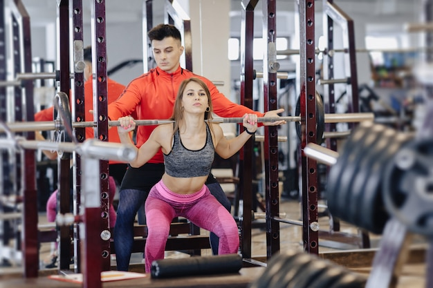 Young girl doing squats with a barbell in the gym under the supervision of a trainer Premium Photo