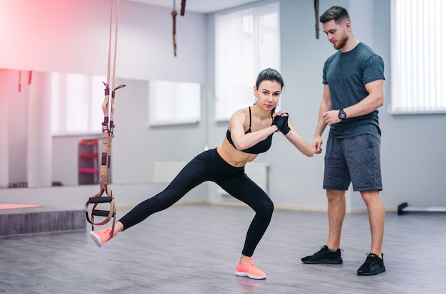 Young girl doing suspension rope exercise together with her personal coach on the gym background. Premium Photo