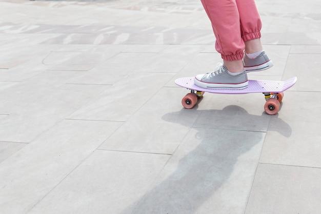 彼女のスケートボードのクローズアップでトリックを行う少女 無料写真