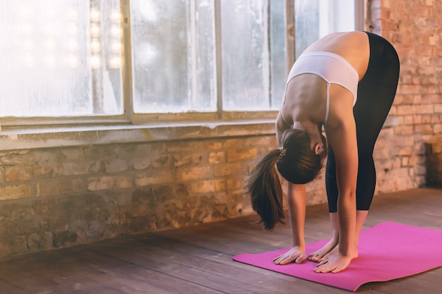 Young girl doing yoga alone in the yoga room near the window Premium Photo