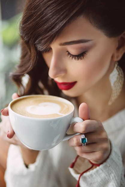 Young girl drinking coffee in a trendy cafe Free Photo
