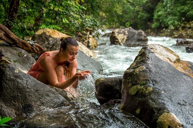Una giovane ragazza beve l'acqua da un ruscello di montagna Foto Gratuite