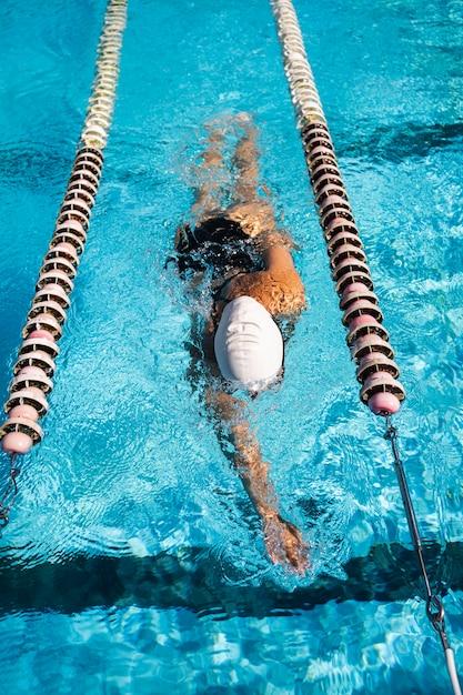 Ragazza giovane godendo di nuotare in piscina Foto Gratuite