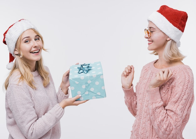 Young girl giving her friend a gift Free Photo