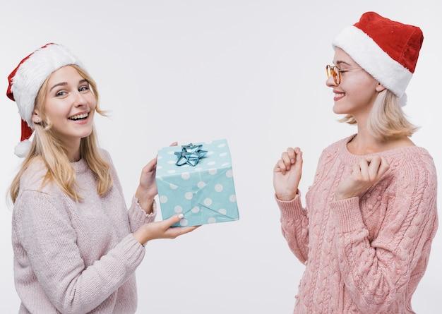 Ragazza che dà al suo amico un regalo Foto Gratuite