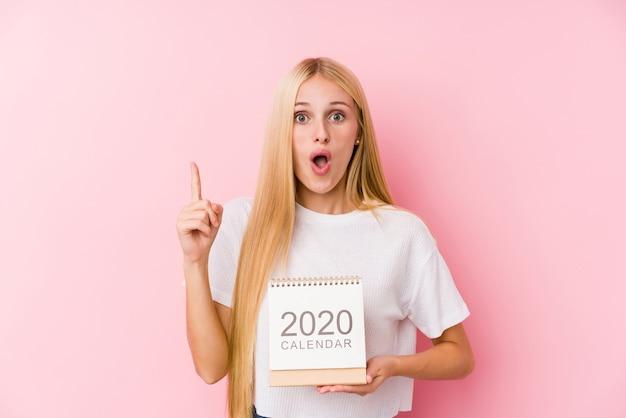 いくつかの素晴らしいアイデア、創造性の概念を持つ2020年カレンダーをもつ少女。 Premium写真