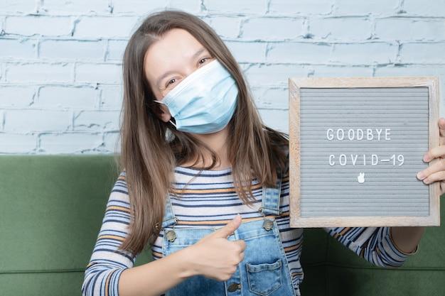 Covidとパンデミックに対してポスターを保持している少女 無料写真