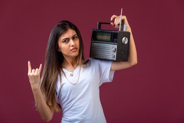 彼女の肩にビンテージラジオを持って、献身的に見える少女。 無料写真
