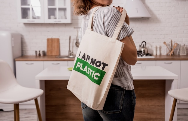 Young girl holding a cloth bag. at the kitchen. i am not plastic. Premium Photo