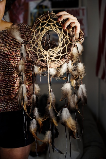 Young girl holding a diy dreamcatcher Free Photo