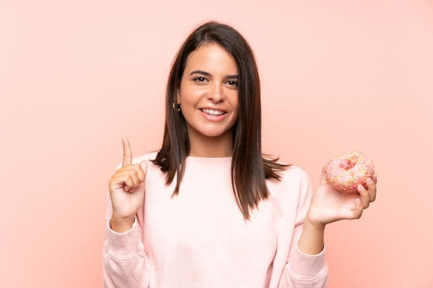 Young girl holding a donut over isolated pink wall pointing up a great idea Premium Photo