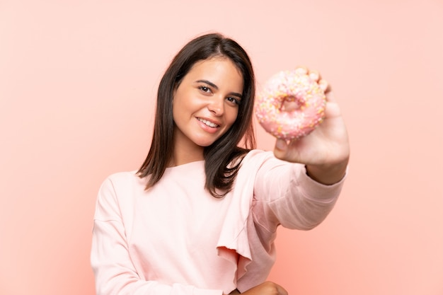 Young girl holding a donut over isolated pink wall Premium Photo