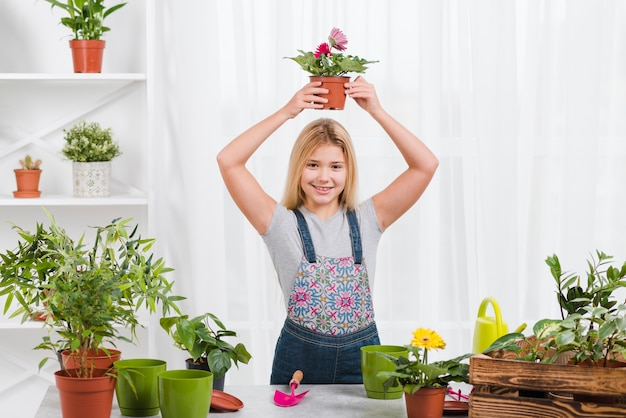 Young girl holding flowers pot Free Photo