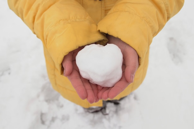 Young girl holding a snowball in her hands in the winter park Premium Photo