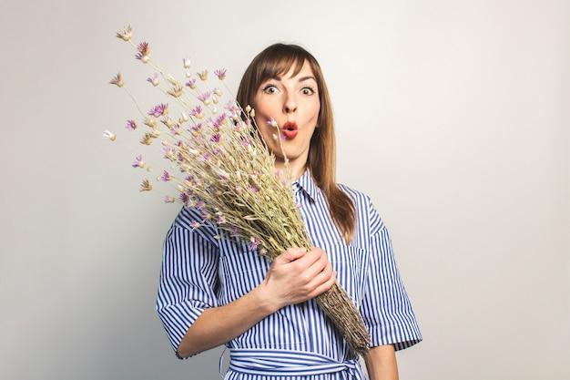 Молодая девушка держит букет полевых цветов, девушка показывает эмоции на светлом фоне Premium Фотографии