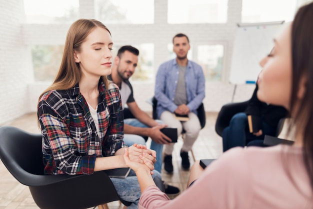 Young girl holds hand of woman during group therapy session Premium Photo