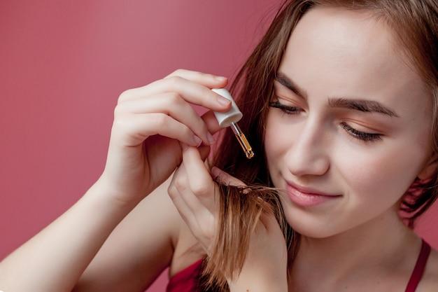 Молодая девушка держит в руках кончики своих волос, а правая рука наносит им желтое масло. Premium Фотографии