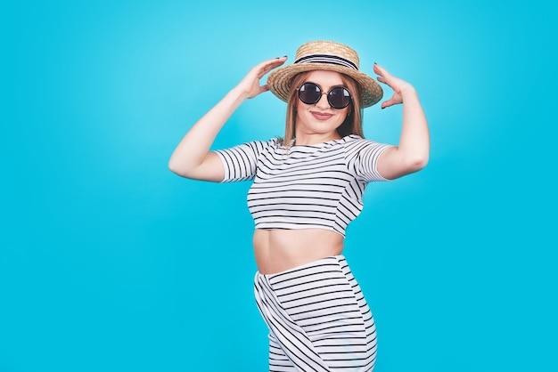 흰색과 검은 색 줄무늬, 모자, 선글라스에 어린 소녀, 완벽한 몸매를 가진 밝은 파란색 배경에 감정적으로 열린 입. 외딴. 스튜디오 촬영. 프리미엄 사진