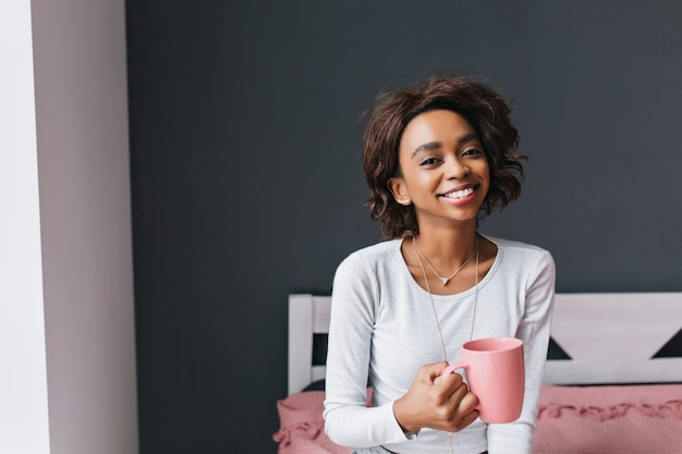 ピンクのカップを保持している、朝のコーヒーを楽しんで、お茶を飲んで、灰色の壁の部屋で笑顔のベッドで若い女の子。彼女は短い巻き毛をしています。ライトグレーのロングスリーブtシャツ。 無料写真