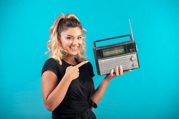 ヴィンテージラジオを保持し、前向きに感じる黒いシャツの少女。 無料写真