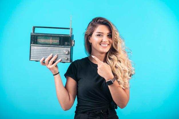 ヴィンテージラジオを持ってそれを指している黒いシャツの少女。 無料写真