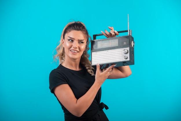 彼女の肩にヴィンテージラジオを保持し、前向きに感じる黒いシャツの少女。 無料写真