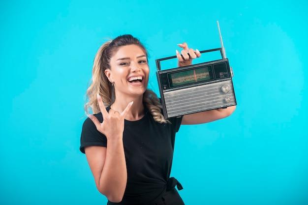 Молодая девушка в черной рубашке держит на плече старинное радио и чувствует себя позитивно. Бесплатные Фотографии