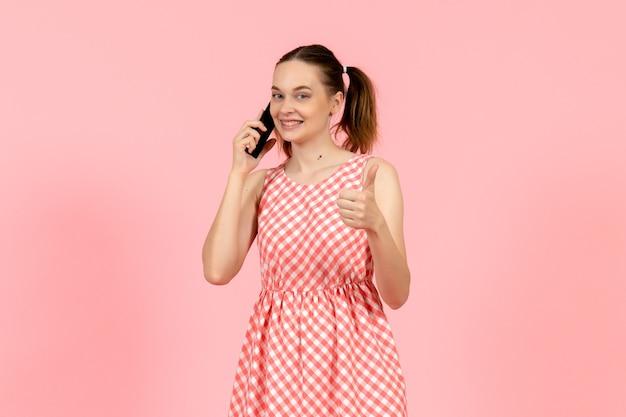 ピンクの笑顔で電話で話しているかわいい明るいドレスの少女 無料写真