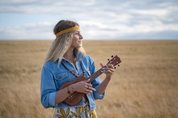 熟したライ麦の黄金のフィールドの背景にウクレレギターとヒッピーの服を着た少女 Premium写真