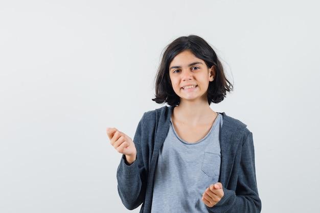 ライトグレーのtシャツとダークグレーのジップフロントのフーディーで拳を握りしめ、かわいく見える少女 無料写真
