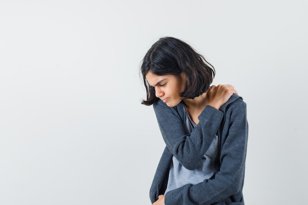 ライトグレーのtシャツとダークグレーのジップフロントフーディーの若い女の子が肩に手を置き、肩の痛みがあり、疲れ果てているように見えます 無料写真