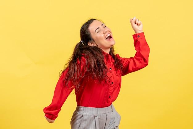 Молодая девушка в красной блузке танцует на желтом Бесплатные Фотографии