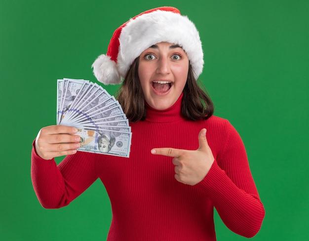 빨간 스웨터와 산타 모자 돈에 검지 손가락으로 가리키는 현금을 들고 어린 소녀 녹색 벽 위에 행복하고 놀란 서 무료 사진