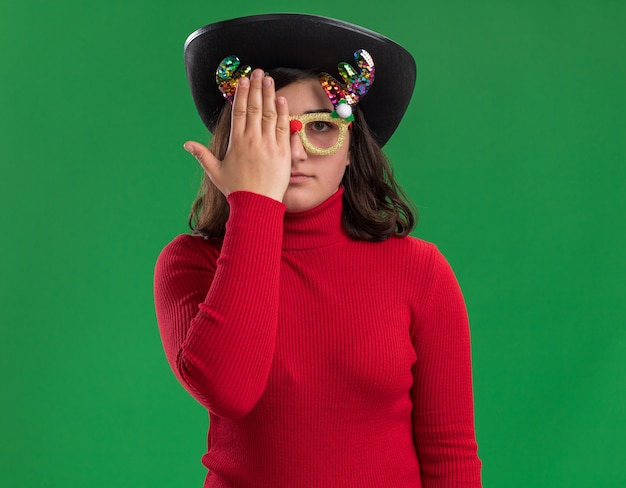 面白い眼鏡と手で片目を覆う黒い帽子を身に着けている赤いセーターの少女 無料写真