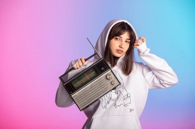 ヴィンテージラジオを持って音楽を聴いているスポーツ衣装の少女。 無料写真