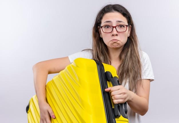 不幸な顔で悲しい表情でカメラを見て旅行スーツケースを保持している白いtシャツの少女 無料写真