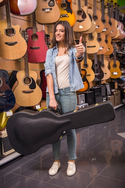 Young girl is holding a guitar in a case. Premium Photo