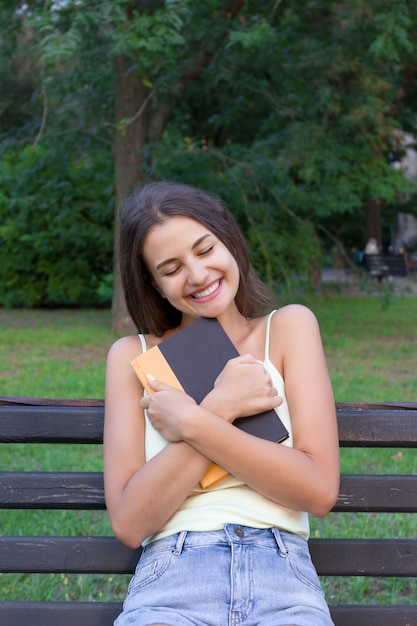 Young girl is hugging her favourite textbook in the park Premium Photo